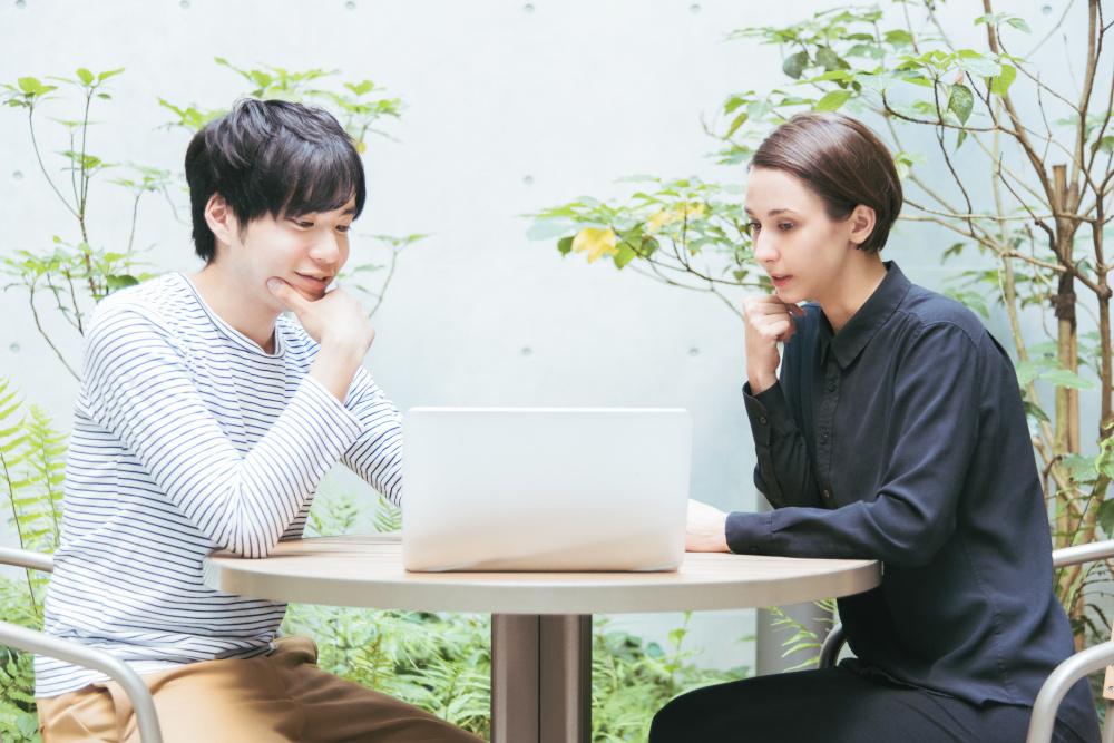 rozmowa kobiety mezczyzny przy stoliku na ktorym znajduje sie laptop