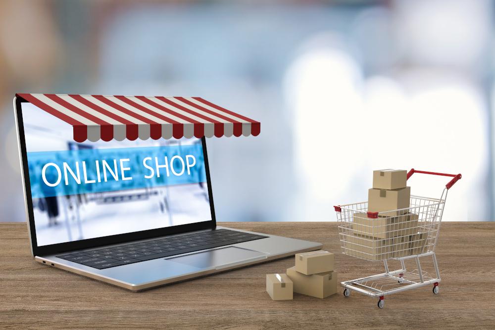 napis na ekranie laptopa online shop oraz wózek z pudełkami obok latopa