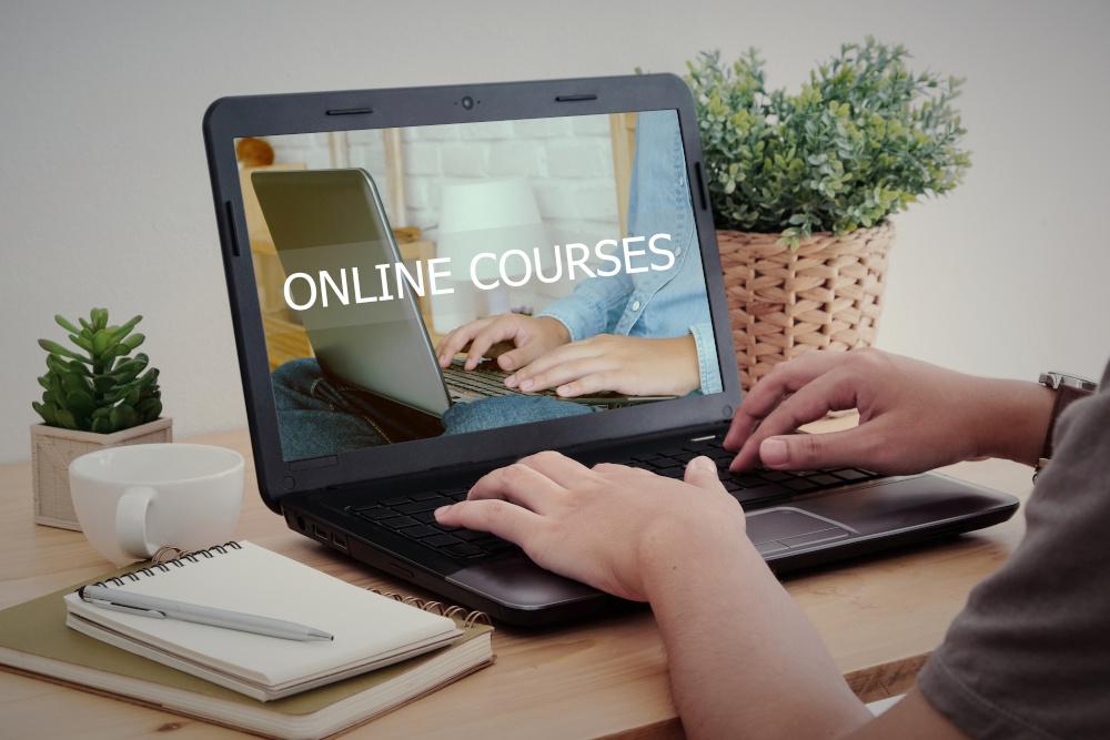 mężczyzna korzystający z laptopa na którym jest napisa online courses