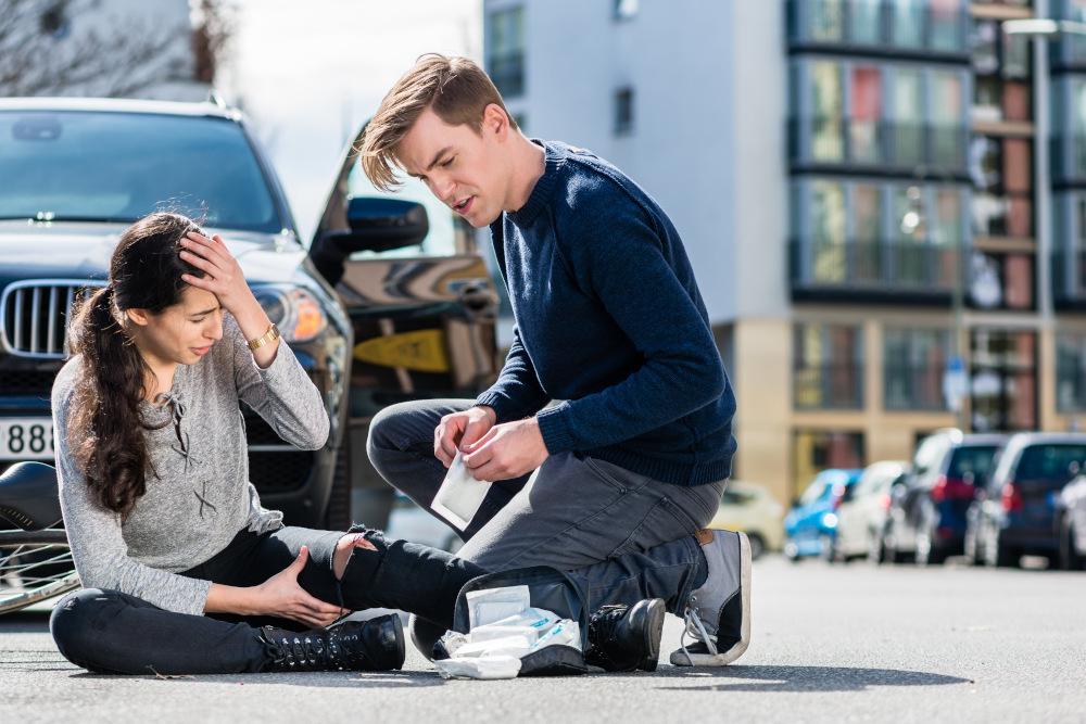 młody kierowca pomaga kobiecie siedzącej na ulicy która doznała urazu